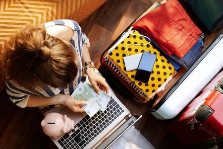 Upper view of young woman in white pants and striped blouse with piggy bank near open travel suitcase holiday budgeting at modern home in sunny summer day. Stok Fotoğraf