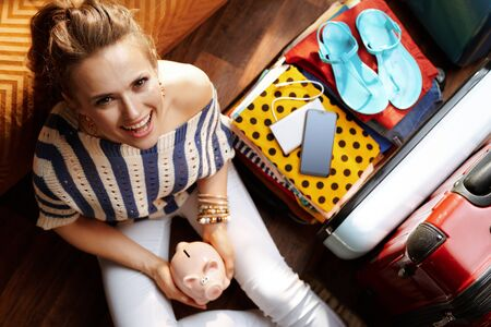 Upper view of happy modern woman in white pants and striped blouse in the modern house in sunny summer day holding piggy bank near open travel suitcase planning economy travel. Stok Fotoğraf