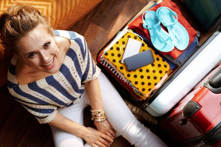 Upper view of smiling young woman in white pants and striped blouse in the modern living room in sunny summer day near open travel suitcase.