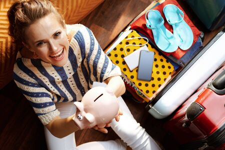 Upper view of happy modern woman in white pants and striped blouse at modern home in sunny summer day showing piggy bank near open travel suitcase planning budget trip. 版權商用圖片 - 124773766