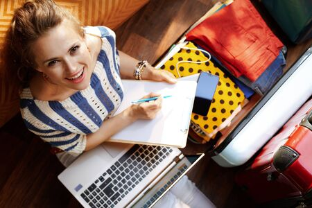 Upper view of smiling modern woman in white pants and striped blouse in the modern living room in sunny summer day filling luggage plan near open travel suitcase. Stok Fotoğraf - 124773772