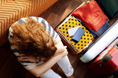Upper view of tired modern woman in white pants and striped blouse at modern home in sunny summer day near open travel suitcase.