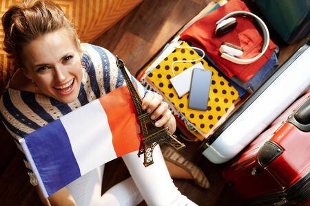 Upper view of happy elegant woman in white pants and striped blouse in the modern house in sunny summer day showing French flag and Eiffel tower souvenir near open travel suitcase. Zdjęcie Seryjne