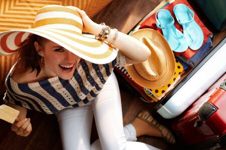 Upper view of happy elegant woman in white pants and striped blouse with big summer hat near open travel suitcase eating ice cream packing for summer holiday in the modern house in sunny summer day. Stok Fotoğraf - 124773770