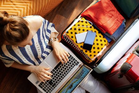 Upper view of elegant woman in white pants and striped blouse in the modern living room in sunny summer day buying airplane ticket near open travel suitcase. Stok Fotoğraf - 124773771