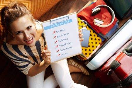 Upper view of smiling modern woman in white pants and striped blouse at modern home in sunny summer day showing packing list near open travel suitcase.