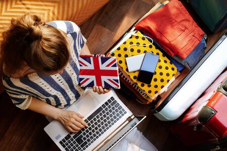 Upper view of stylish woman in white pants and striped blouse with Great Britain flag notebook buying airplane ticket near open travel suitcase in the modern living room in sunny summer day. Stok Fotoğraf - 124773775