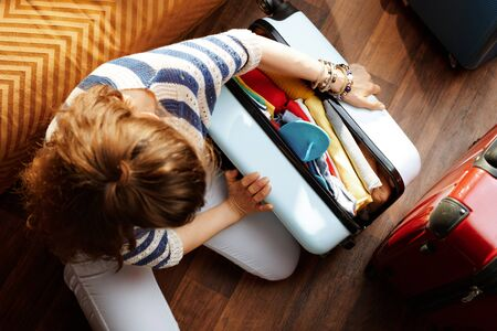 Upper view of stylish woman in white pants and striped blouse in the modern living room in sunny summer day closing over packed suitcase. Stok Fotoğraf - 124773776