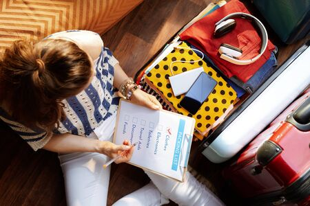 Upper view of elegant woman in white pants and striped blouse with packing list near open travel suitcase at modern home in sunny summer day. Stok Fotoğraf - 124779686