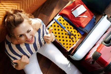 Upper view of smiling young woman in white pants and striped blouse in the modern house in sunny summer day showing thumbs up near open travel suitcase.