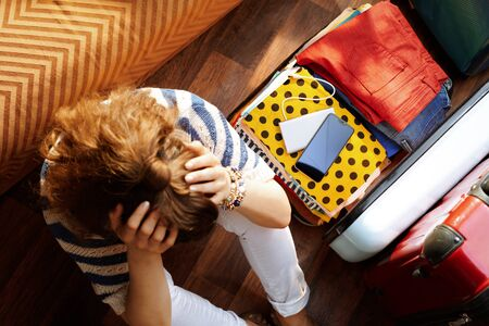 Upper view of stressed young woman in white pants and striped blouse in the modern living room in sunny summer day near open travel suitcase. Stok Fotoğraf - 124779689