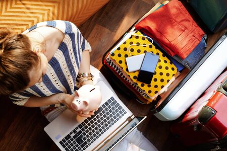 Upper view of elegant woman in white pants and striped blouse in the modern house in sunny summer day holding piggy bank near open travel suitcase planning low cost summer holiday. Stok Fotoğraf