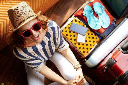 Upper view of happy stylish woman in white pants and striped blouse with supper hat and sunglasses near open travel suitcase in the modern living room in sunny summer day. Stok Fotoğraf - 124779694