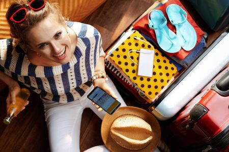 Upper view of smiling elegant woman in white pants and striped blouse at modern home in sunny summer day using mobile travel agent app on smartphone near open travel suitcase. Stok Fotoğraf - 124779696