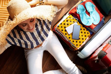 Upper view of happy stylish woman in white pants and striped blouse with big summer straw hat near open travel suitcase packing for summer vacation at modern home in sunny summer day. Stok Fotoğraf - 124779697