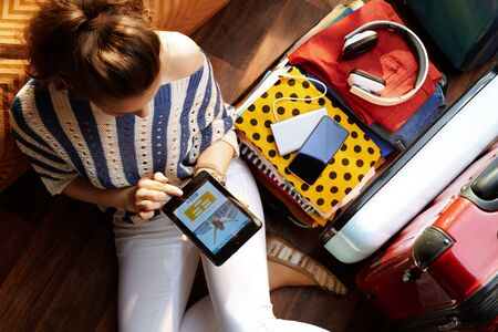 Upper view of elegant woman in white pants and striped blouse at modern home in sunny summer day book flight on phone near open travel suitcase.