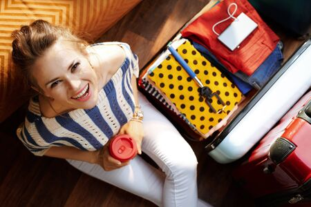 Upper view of happy stylish woman in white pants and striped blouse with coffee cup near open travel suitcase in the modern house in sunny summer day.