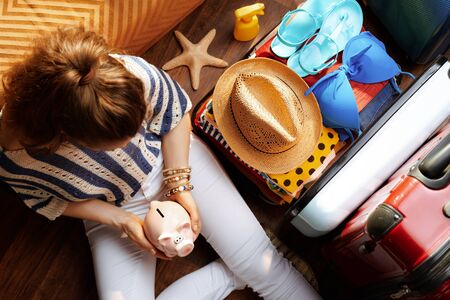 Upper view of stylish woman in white pants and striped blouse at modern home in sunny summer day holding piggy bank near open travel suitcase. Stok Fotoğraf - 124779701