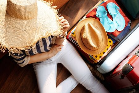 Upper view of modern woman in white pants and striped blouse with big summer hat near open travel suitcase planning summer vacation in the modern house in sunny summer day.