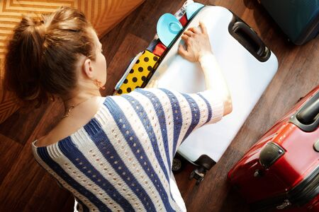 Upper view of modern woman in white pants and striped blouse in the modern house in sunny summer day closing over packed suitcase. Stok Fotoğraf - 124779703