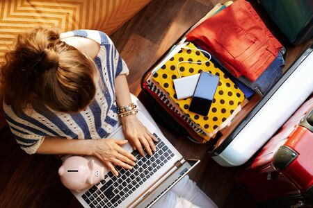 Upper view of stylish woman in white pants and striped blouse with piggy bank near open travel suitcase booking economy hotel online at modern home in sunny summer day. Stok Fotoğraf - 124779704