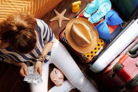 Upper view of modern woman in white pants and striped blouse with piggy bank counts summer budget money near open travel suitcase in the modern house in sunny summer day. Stok Fotoğraf - 124779705