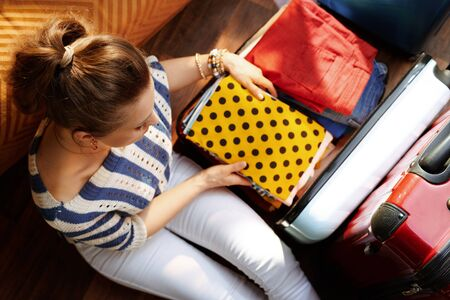 Upper view of elegant woman in white pants and striped blouse in the modern house in sunny summer day putting stuff in an open travel suitcase. Stok Fotoğraf - 124779706