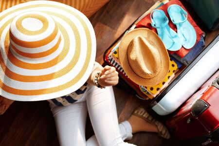 Upper view of modern woman in white pants and striped blouse with big summer hat near open travel suitcase packing for summer holiday at modern home in sunny summer day.