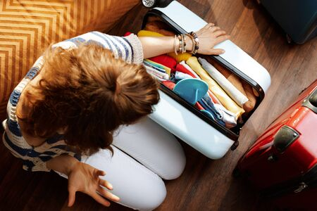 Upper view of furious modern woman in white pants and striped blouse in the modern living room in sunny summer day closing over packed suitcase.