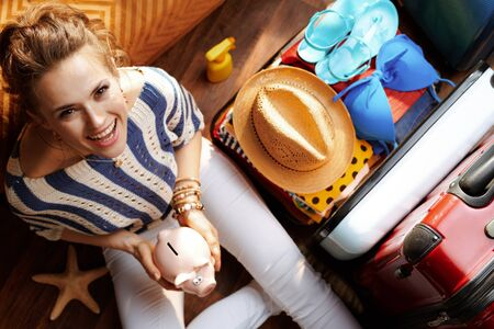 Upper view of smiling elegant woman in white pants and striped blouse in the modern living room in sunny summer day holding piggy bank near open travel suitcase. Stok Fotoğraf - 124779709