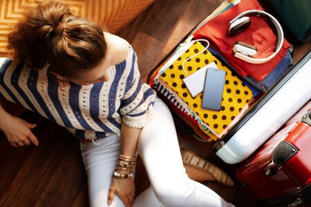 Upper view of relaxed young woman in white pants and striped blouse at modern home in sunny summer day near open travel suitcase.