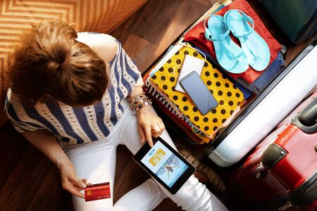 Upper view of young woman in white pants and striped blouse at modern home in sunny summer day book flight on tablet PC near open travel suitcase. Stok Fotoğraf - 124779711