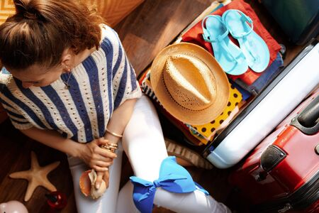 Upper view of stylish woman in white pants and striped blouse near open travel suitcase with summer holiday stuff in the modern living room in sunny summer day. Stok Fotoğraf