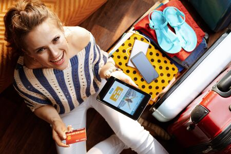 Upper view of smiling young woman in white pants and striped blouse at modern home in sunny summer day buying tickets online on tablet PC near open travel suitcase. Stok Fotoğraf