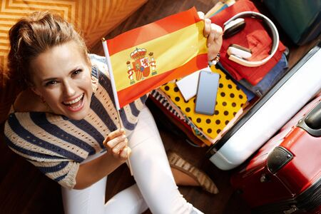 Upper view of happy stylish woman in white pants and striped blouse in the modern house in sunny summer day showing Spanish flag near open travel suitcase. Stock Photo