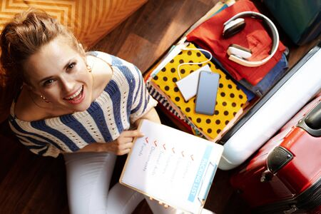 Upper view of smiling young woman in white pants and striped blouse with packing list near open travel suitcase at modern home in sunny summer day.
