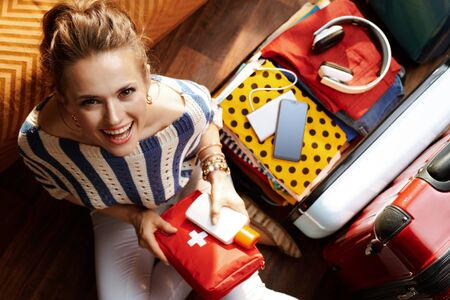 Upper view of smiling young woman in white pants and striped blouse with first aid kit near open travel suitcase at modern home in sunny summer day. Stok Fotoğraf - 124779717