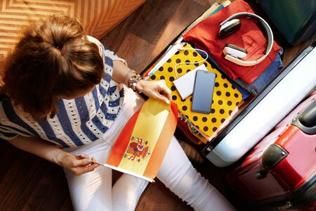 Upper view of stylish woman in white pants and striped blouse with Spanish flag near open travel suitcase at modern home in sunny summer day.
