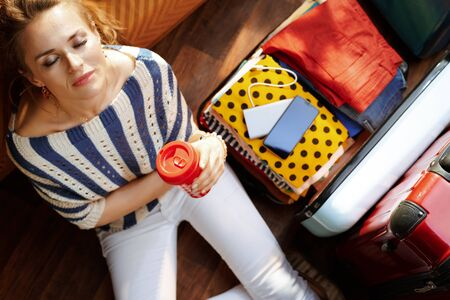 Upper view of relaxed elegant woman in white pants and striped blouse with coffee cup near open travel suitcase in the modern house in sunny summer day.