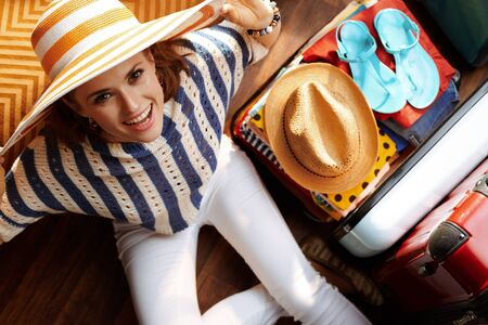 Upper view of happy modern woman in white pants and striped blouse with big summer hat near open travel suitcase packing for summer holiday at modern home in sunny summer day.