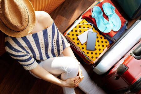 Upper view of relaxed stylish woman in white pants and striped blouse with straw hat near open travel suitcase in the modern living room in sunny summer day. Stok Fotoğraf - 124779721