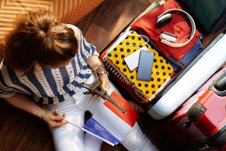 Upper view of stylish woman in white pants and striped blouse with French flag and Eiffel tower souvenir near open travel suitcase at modern home in sunny summer day. Stock Photo