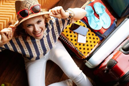 Upper view of smiling elegant woman in white pants and striped blouse with supper hat and sunglasses near open travel suitcase in the modern living room in sunny summer day. Stok Fotoğraf - 124779723