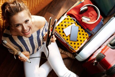 Upper view of smiling young woman in white pants and striped blouse in the modern living room in sunny summer day showing hair curler and iron near open travel suitcase.