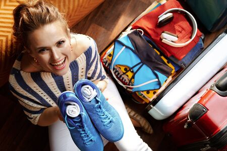 Upper view of happy elegant woman in white pants and striped blouse in the modern house in sunny summer day packing fitness gear near open travel suitcase to stay fit while having summer holidays.