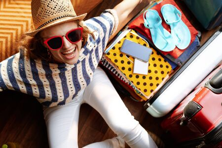 Upper view of cheerful stylish woman in white pants and striped blouse with supper hat and sunglasses near open travel suitcase at modern home in sunny summer day. Stok Fotoğraf - 124780737