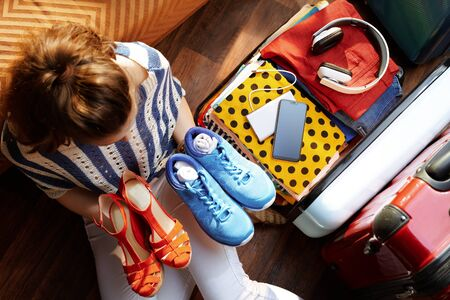 Upper view of young woman in white pants and striped blouse at modern home in sunny summer day packing fashion and comfortable shoes in open travel suitcase. Stock Photo