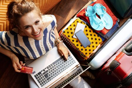 Upper view of smiling stylish woman in white pants and striped blouse with credit card and laptop booking hotel online near open travel suitcase in the modern house in sunny summer day.