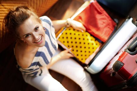 Upper view of happy elegant woman in white pants and striped blouse in the modern house in sunny summer day packing stuff in open travel suitcase.