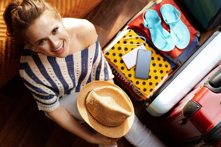 Upper view of happy young woman in white pants and striped blouse with straw hat near open travel suitcase in the modern house in sunny summer day.